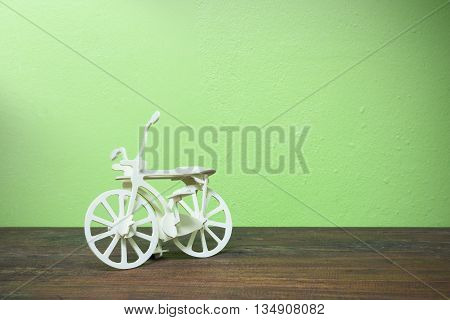 Wooden bicycle Toy on old wood and green wall background