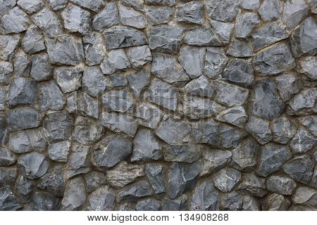 rough stone wall background texture closeup on noon time