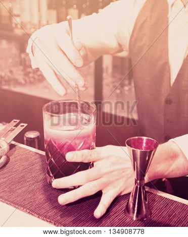 Bartender is stirring a shrub cocktail with sparkling wine, toned image