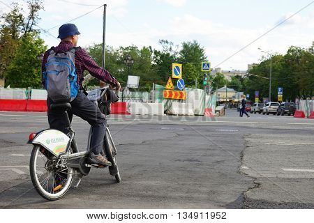 MOSCOW, RUSSIA - MAY 15, 2016: A man on a bicycle on the roadway. Reconstruction of the roadway within the city beautification program My Street in Moscow.