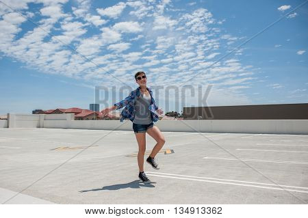 Teenage girl with crew cut running carefree under blue cloudy sky.