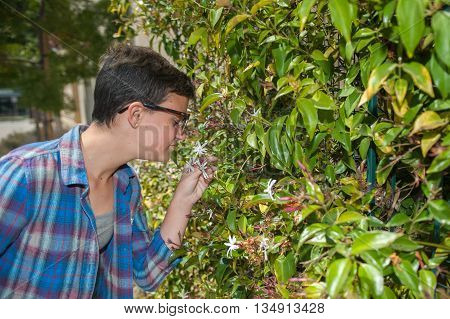 Teenage girl with crew cut smelling the jasmine flowers.