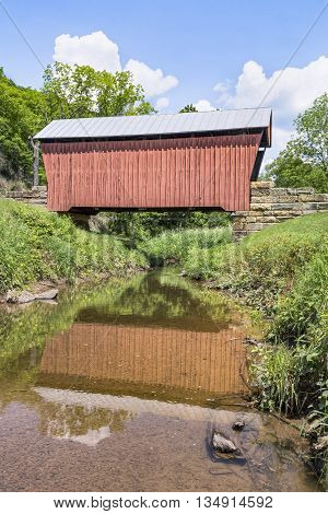 Built in 1888 Center Point Covered Bridge is reflected on the waters of The Talkington Fork of McElroy Creek in rural Doddridge County West Virginia.