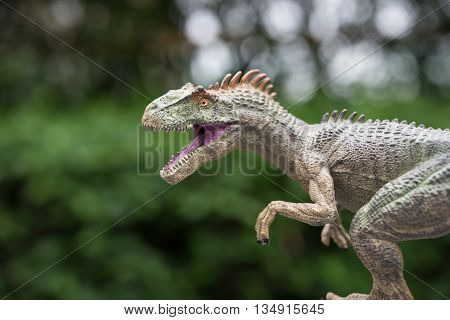 an allosaurus toy in front of trees