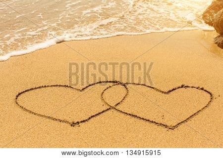 A pair of hearts drawn on sand beach with the soft wave.