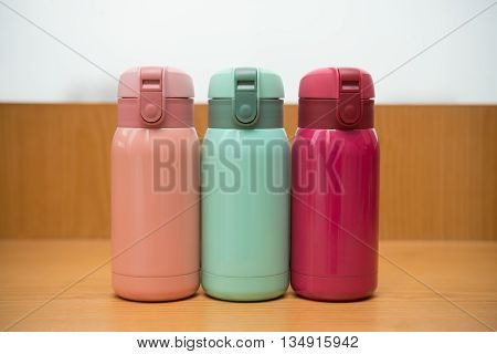 three colorful thermos on a wooden table