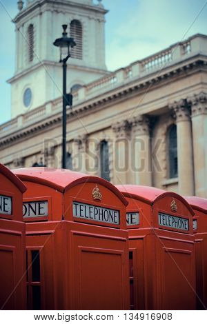 Red telephone box in street with historical architecture in London.