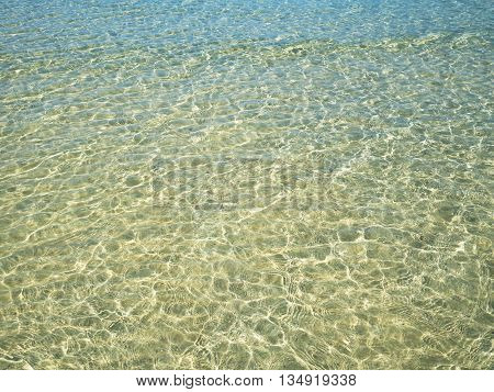 Background of transparent crystal green blue sea water surface ripple with sun reflection in summer. Water background. Ocean water texture.
