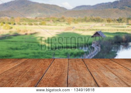 Perspective wooden with green rice field blurred background, stock photo