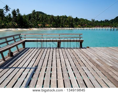 Wood chair on wooden bridge with blue sea sky and resort in background. Vacation tourism and summer concept. Tropical resort.