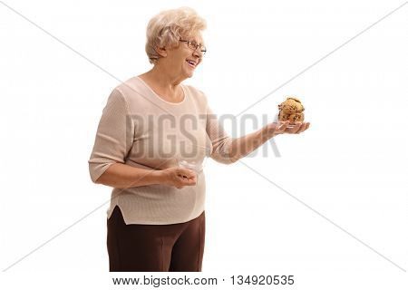 Senior woman holding a jar of cookies and offering them to someone isolated on white background