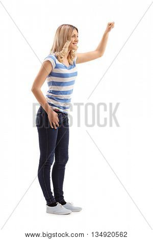 Full length profile shot of a young blond woman knocking on a door isolated on white background