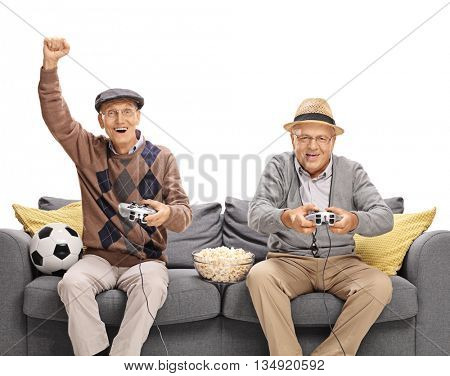 Two seniors playing football video game seated on a couch isolated on white background