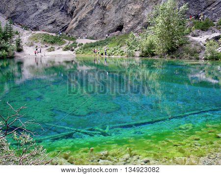 clear blue mountain lake, hiking trail lakeside.