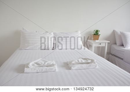 white king size bed two pillows towel and tree pot plant in bedroom for rest and relax feel comfortable