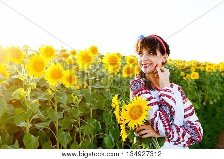 Beautiful young woman in national ukrainian blouse embrodery holding three sunflowers on a plant at sunset backlight.