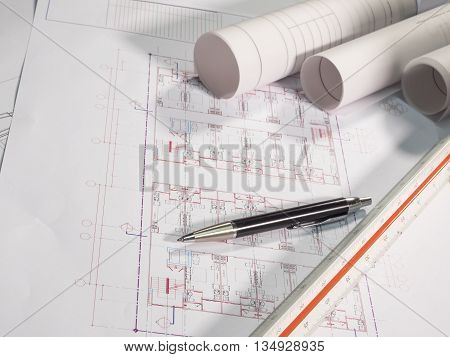 Architect rolls and plans technical project drawing and pen on table (Selective focus)