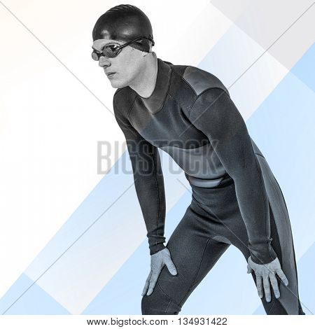 Swimmer in wetsuit and swimming goggles against colored background