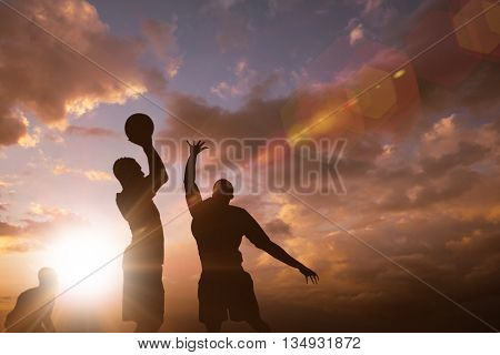 Football player getting ready for a throw against clouds