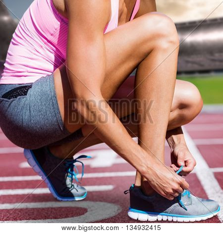 Close up of sportswoman is lacing shoes against race track