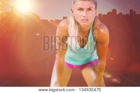 Exhausted woman after her run against cityscape on sunlight