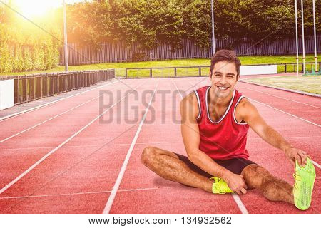 Portrait of male athlete stretching his hamstring against race track