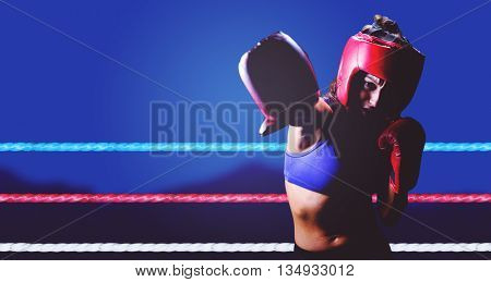 Female boxer with gloves and headgear punching against blurred mountains