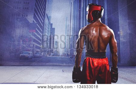 Rear view of boxer standing against urban projection on wall
