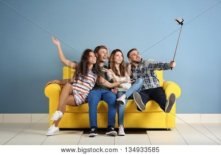 Young cheerful friends taking selfie on yellow sofa in the room