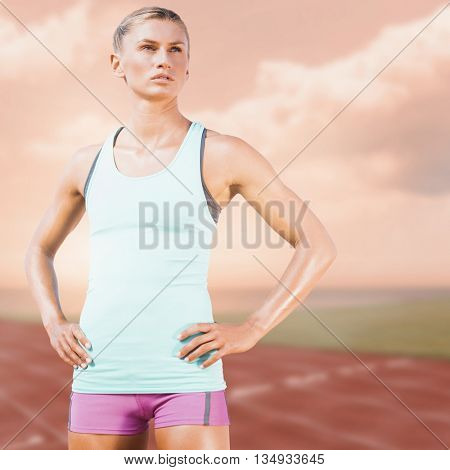 Sporty woman posing against composite image of race track in front of the ocean
