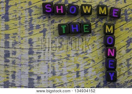 SHOW ME THE MONEY words with dices on old wooden background