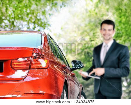 Red car and businessman with tablet outdoors