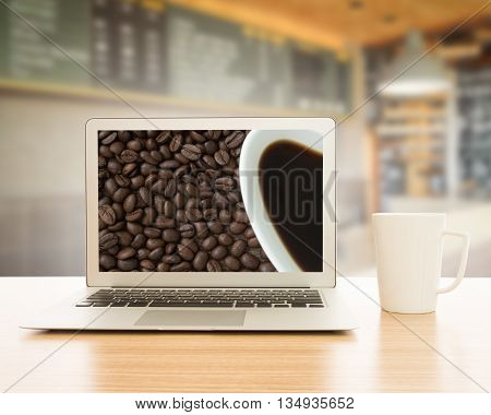labtop and cup of coffee on table in cafe.