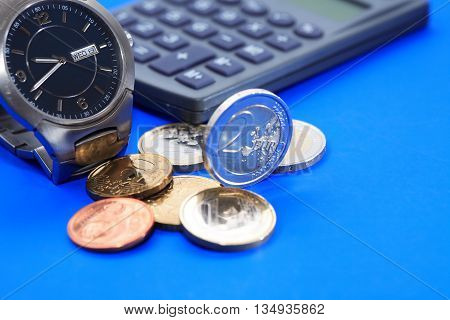 Set of European coins near wristwatch and calculator on blue background