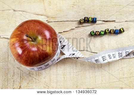 Diet concept with red and yellow apples and white measuring tape on wooden table