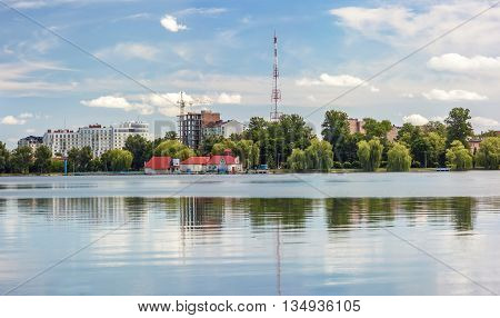 Modern city reflected in a mirror like lake wiht green trees