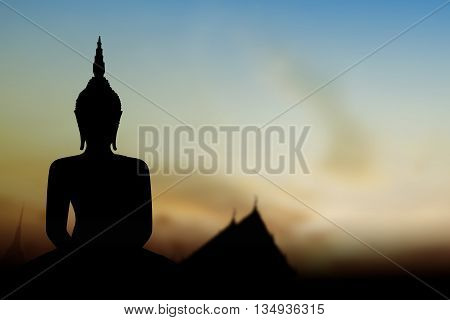 Silhouette public Buddha statue over sunset in Thailand background.