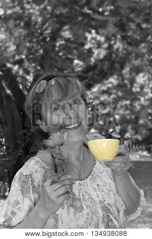 Middle aged woman with a happy look on her face posing with a flower and tea cup in front of trees. Selective color outdoor shot