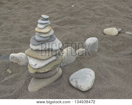 stones stacked in a pyramid, lying on the sand
