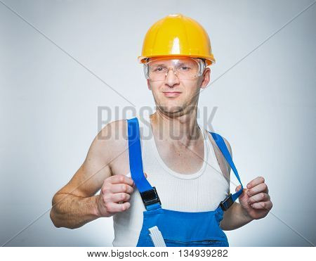 Funny lazy builder isolated on gray. Studio shot close up