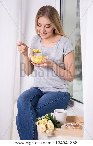 Morning - Portrait Of Young Woman Having Breakfast With Corn Flakes At Home