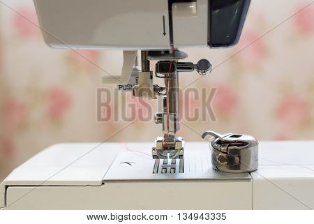 Red needle placed in a white sewing machine