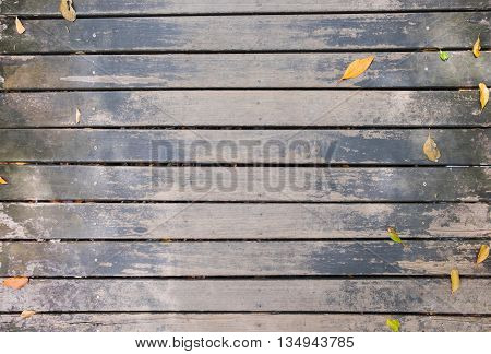 Top view of wooden walkway bridge with dry leaves for background and texture.