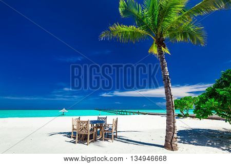 Tables and chairs in the shadow of palm tree on amazing tropical island