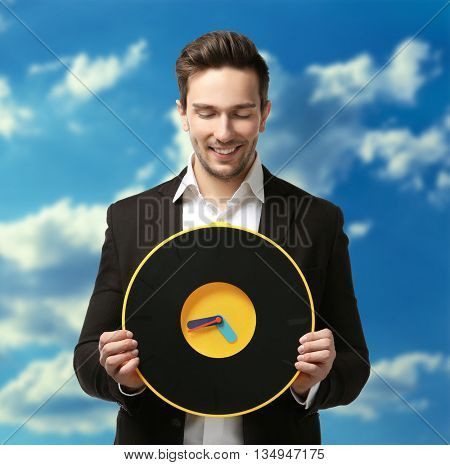 Man in black suit holding big clock on sky background