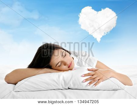 Beautiful girl lying on blue cloudy sky and dreaming about love