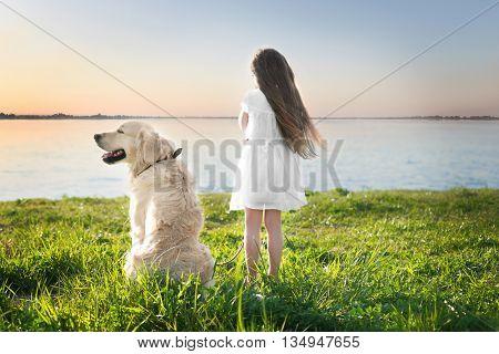Little girl and big kind dog on the riverside