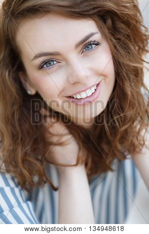 Beautiful girl with grey eyes and long curly red hair,a nice smile and straight white teeth,light makeup,wearing earrings,wearing a light striped shirt,posing for photographer during the summer in the fresh air