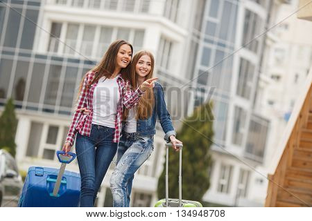 Beautiful girlfriend,two young women,a brunette with long straight hair,cute smile,dressed in blue jeans,a white t-shirt,plaid shirt and blue jacket,with blue and green suitcases on wheels posing at the square near the building of the airport