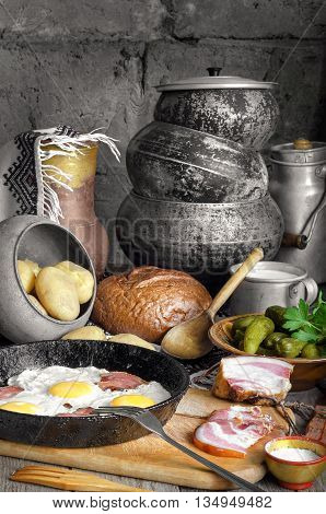 Bacon and eggs boiled potatoes pickles. On the background of antique dishes and bread.